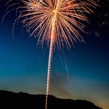 Summer fireworks on display against a backdrop of mountains.