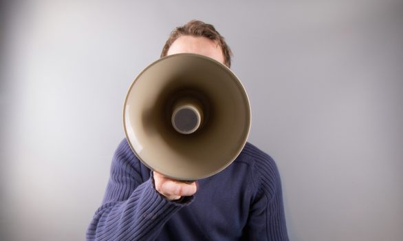 A man with a megaphone influencing others