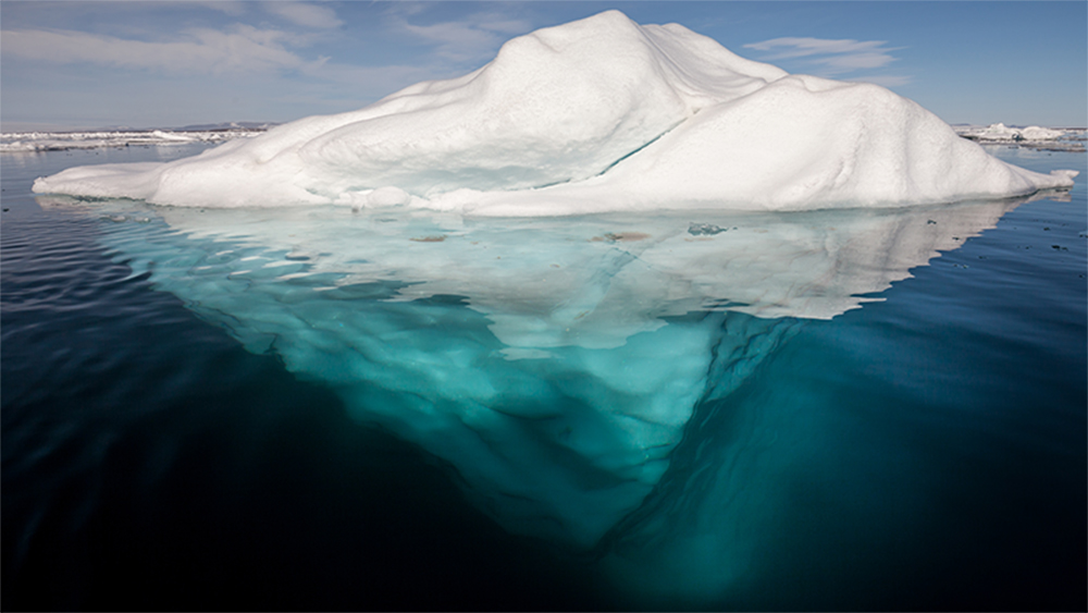 Iceberg_in_the_Arctic_with_its_underside_exposed,_brightened_underwater